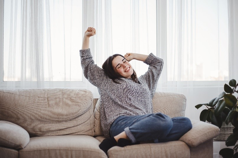 woman relaxing on sofa in rental apartment